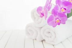 Белые полотенца ванны и цветок орхидеи Стоковые Изображения