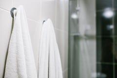 Белые полотенца висят на стене в ванной комнате Чистота, ливень стоковые фото