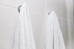 Белые полотенца висят на стене в ванной комнате Чистота, ливень стоковые фотографии rf