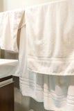 Белые полотенца вися в ванной комнате Стоковые Фотографии RF