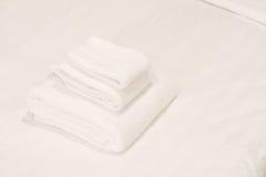Белые полотенца на кровати Стоковые Фото