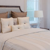 Белые подушки на белой кровати с роскошной лампой Стоковое Фото