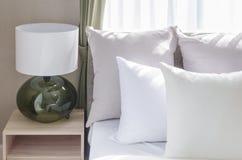 Белые подушки на современной белой кровати с современной лампой Стоковые Фото