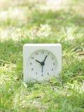 Белые простые часы на дворе лужайки, 10:05 10 5 Стоковое фото RF