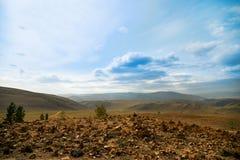 Белые, пушистые облака плавая в голубое небо над зелеными холмами и долина Стоковые Фото