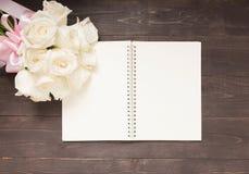 Белые розы цветут с лентой на тетради Стоковая Фотография RF