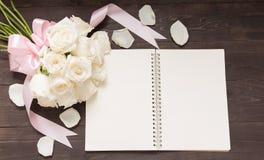 Белые розы цветут с лентой на noteboo Стоковые Изображения RF