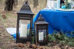 Белые свечи в фонариках в лесе около таблицы банкета свадьбы стоковые изображения rf