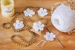 Белые снежинки вязания крючком на подарке и свече на деревянном столе для Стоковое Изображение