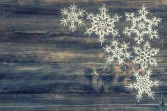 Белые снежинки над деревенской деревянной предпосылкой декорумы рождества Стоковое Изображение