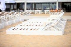 Белые стулья бассейна на пляже песка Стоковые Изображения RF
