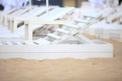 Белые стулья бассейна на пляже песка Стоковое Изображение RF