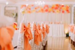 Белые стулья с оранжевым украшением ленты на роскошной зале свадьбы Стоковое фото RF