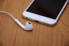 Белые телефон и наушники на деревянной предпосылке стоковые изображения