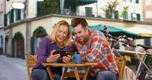 Белые тысячелетние пары смеясь над и имея полезного временем работы вне кофейни Стоковые Фотографии RF