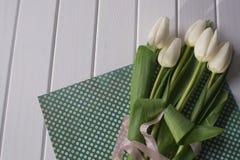 Белые тюльпаны на белой деревянной предпосылке Стоковые Изображения RF
