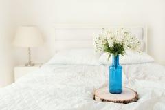 Белые цветки в цветочном горшке бутылки синего стекла Стоковое фото RF