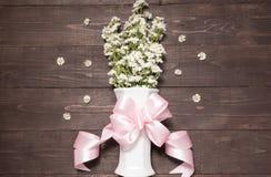 Белые цветки резца в вазе с лентой на деревянном b Стоковые Фотографии RF