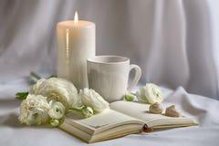 Белые цветки, чашка, свеча и тетрадь на белой предпосылке Стоковое Изображение RF