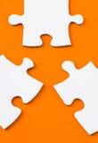 Белые части головоломки на оранжевой предпосылке Стоковое Изображение RF
