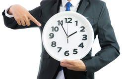 Белые часы держа в руках бизнесмена изолированными Стоковое Изображение