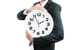 Белые часы держа в руках бизнесмена изолированными Стоковая Фотография
