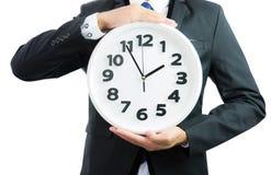Белые часы держа в руках бизнесмена изолированными Стоковые Изображения