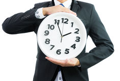 Белые часы держа в руках бизнесмена изолированными Стоковые Фото