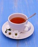 Белые чашка и цветки чая на голубое деревянном Стоковое Изображение