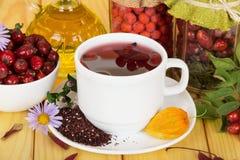 Белые чашка с питьем от ягод золы горы и одичалое подняли на древесину света предпосылки Стоковые Фото