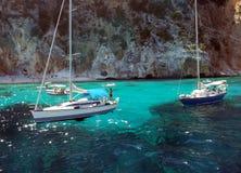 Белые шлюпки в голубом море ‹Сардинии †‹â€ с эффектными утесами Стоковые Фотографии RF
