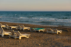 Белые sunbeds в песчаном пляже на заходе солнца Стоковые Фото