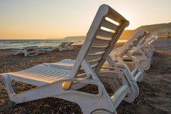 Белые sunbeds в песчаном пляже на заходе солнца Стоковая Фотография RF