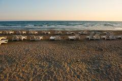 Белые sunbeds в песчаном пляже на заходе солнца Стоковые Изображения
