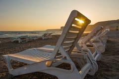 Белые sunbeds в песчаном пляже на заходе солнца Стоковое Фото