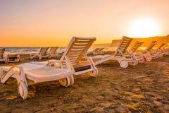 Белые sunbeds в песчаном пляже на заходе солнца Стоковые Изображения RF