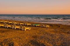 Белые sunbeds в песчаном пляже на заходе солнца Стоковая Фотография