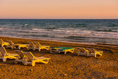 Белые sunbeds в песчаном пляже на заходе солнца Стоковое фото RF