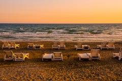 Белые sunbeds в песчаном пляже на заходе солнца Стоковое Изображение