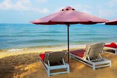 Белые sunbeds и зонтик на пляже моря Стоковое Изображение