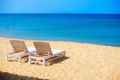 Белые sunbeds на одичалом пляже моря Стоковая Фотография