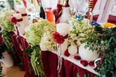 Белые wedding свечи украшенные с красными розами и лентами Стоковые Изображения