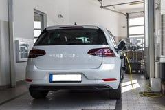 Белый автомобиль который поручен с электричеством Новое поколение автомобилей Стоковая Фотография