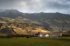 Белый амбар с красной крышей в зеленом цвете хранил surround горной цепью Стоковые Изображения