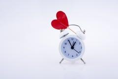 Белый будильник цвета и красная форма сердца Стоковое Фото