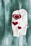 Белый грейте связанные mittens над деревянной предпосылкой Стоковое фото RF