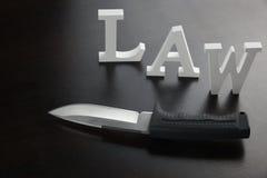 Белый закон и нож знака на черной предпосылке Стоковое Изображение