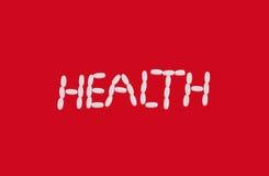 Белый знак здоровья пилюлек на красной предпосылке Стоковые Фотографии RF