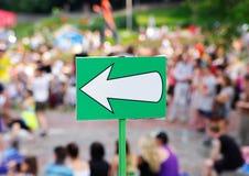 Белый знак стрелки против толпы Стоковые Фото