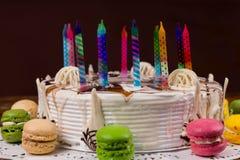 Белый именниный пирог с сериями покрашенных свечей приближает к различной Стоковое Изображение RF